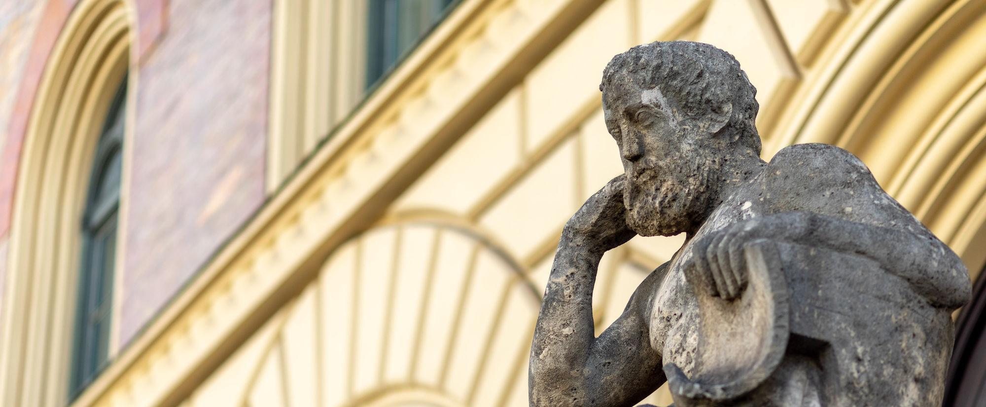 Skulptur in München - Mann in nachdenklicher Pose auf einem Sessel
